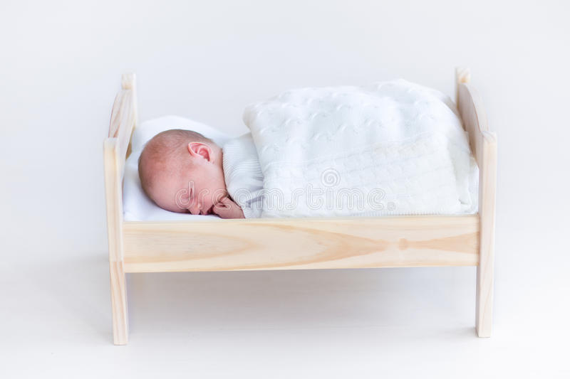 Tiny newborn baby sleeping in a toy crib. Under a white blanket stock photo