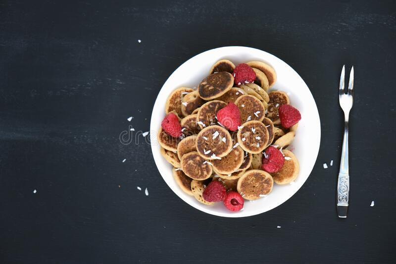 Tiny pancake cereal - trendy quarantine food. Mini pancakes in bowl with fresh raspberries and coconut flakes on black background royalty free stock photos