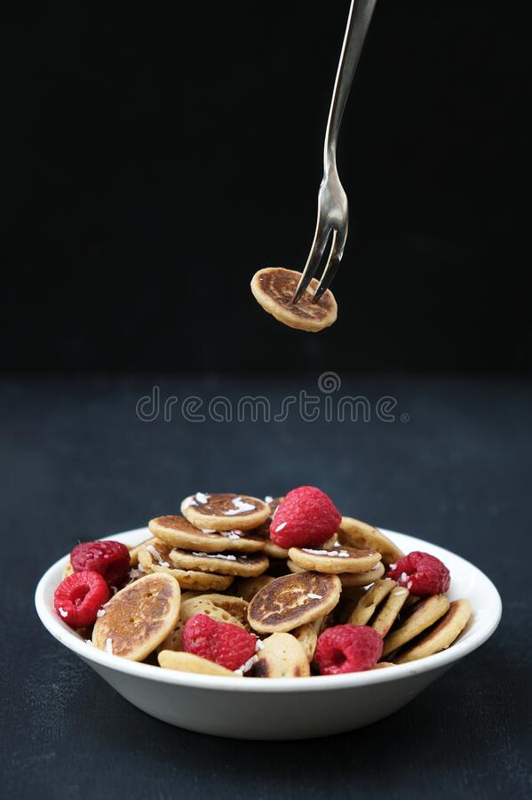 Tiny pancake cereal - trendy quarantine food. Mini pancakes in bowl with fresh raspberries and coconut flakes and fork with one royalty free stock photos