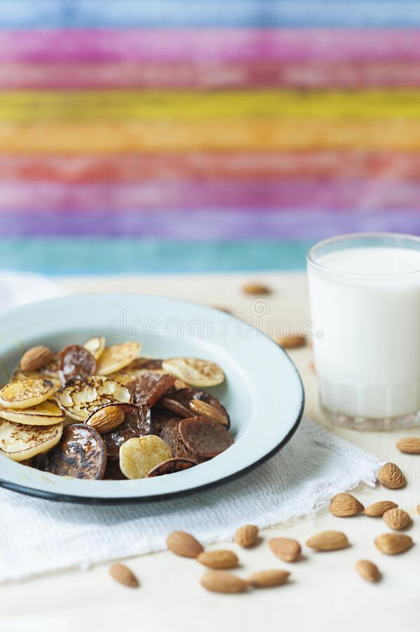 Tiny pancakes with almond nuts and honey in metal plate on colorful bright kitchen with milk cup. trending food cereal pancakes. Bright and beautiful Breakfast stock photo