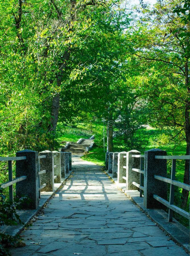 Tiny pedestrian bridge leading to a park stock photography