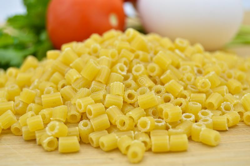 Tiny pieces of macaroni, parsley, tomatoes and egg. Isolated on cutting board royalty free stock photo