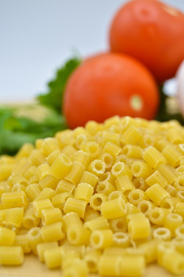 Tiny pieces of macaroni, parsley, tomatoes. Isolated on cutting board stock photos