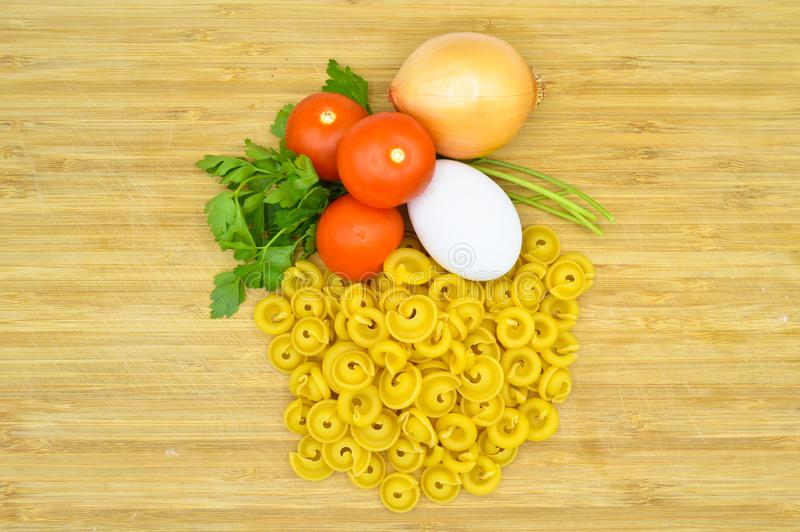 Tiny pieces of macaroni, tomatoes, egg and onion. Tiny pieces of macaroni, tomatoes and egg isolated on cutting board royalty free stock image