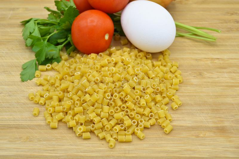 Tiny pieces of macaroni, tomatoes and egg. Isolated on cutting board royalty free stock photography