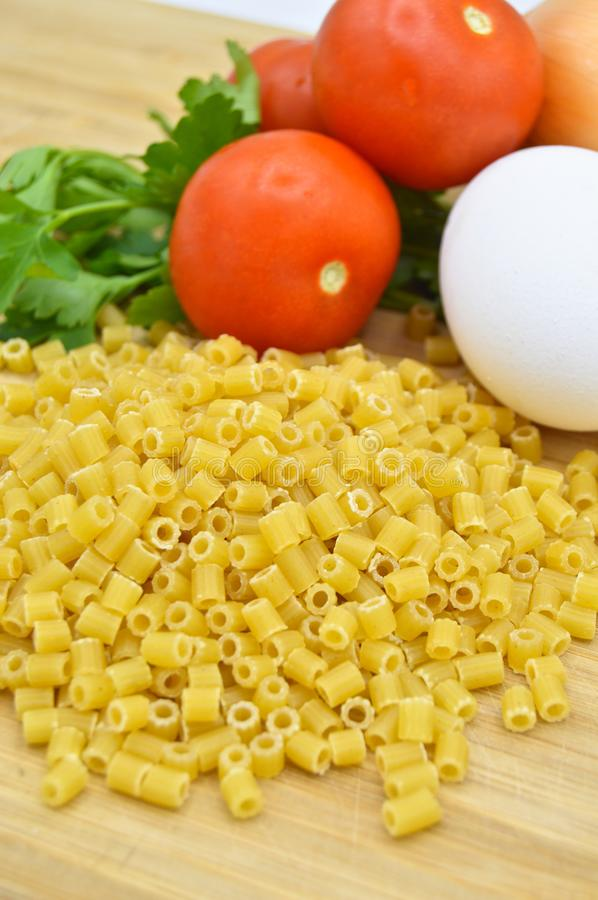 Tiny pieces of macaroni, tomatoes, egg and onion. Tiny pieces of macaroni, tomatoes and egg isolated on cutting board royalty free stock photos