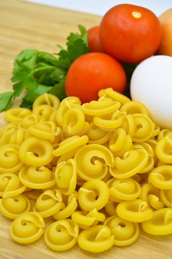 Tiny pieces of macaroni, tomatoes, egg and onion. Tiny pieces of macaroni, tomatoes and egg isolated on cutting board stock photography