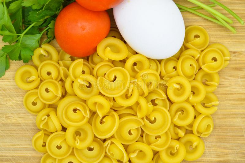 Tiny pieces of macaroni, tomatoes and egg. Isolated on cutting board royalty free stock photo