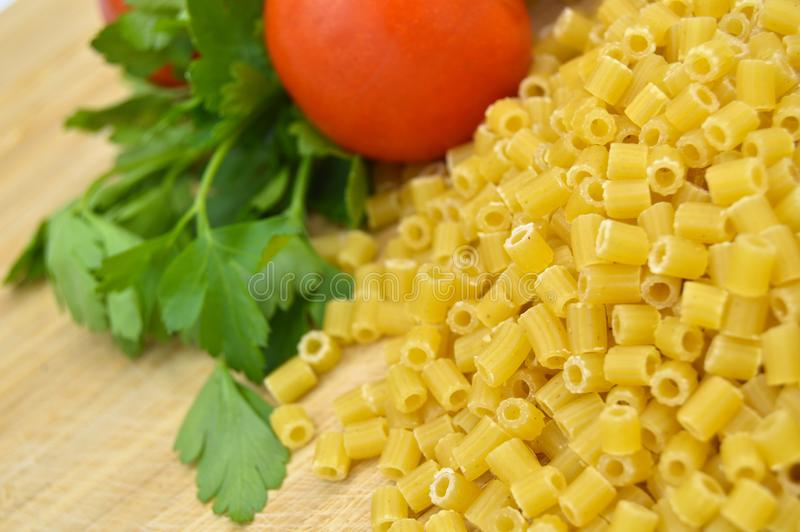Tiny pieces of macaroni, tomatoes and parsley. Tiny pieces of macaroni, tomatoes and egg isolated on cutting board stock photo