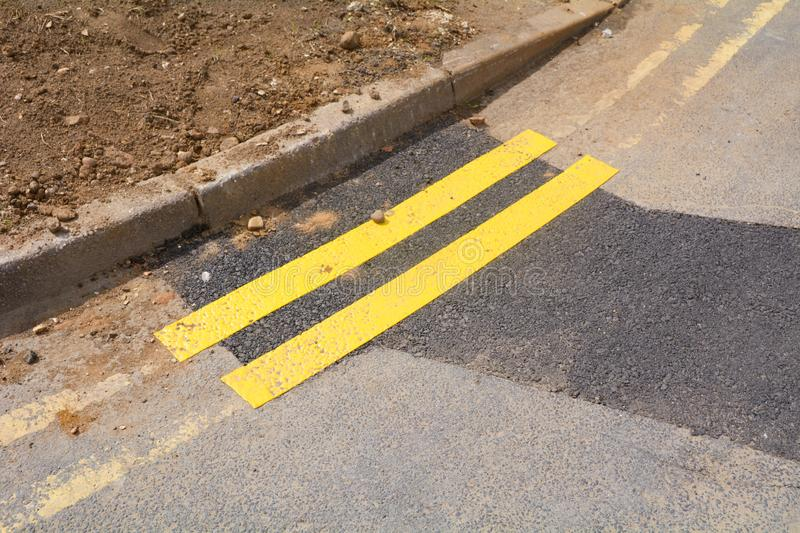 Tiny section of newly painted double yellow lines on road. Next to kerb royalty free stock photos
