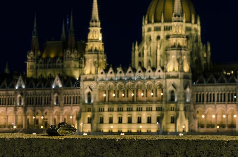 Tiny tank sculpture on the wall by the Danube river, Parliament building in the background, Budapest, Hungary. Budapest, Hungary - 12/24/2017 stock image