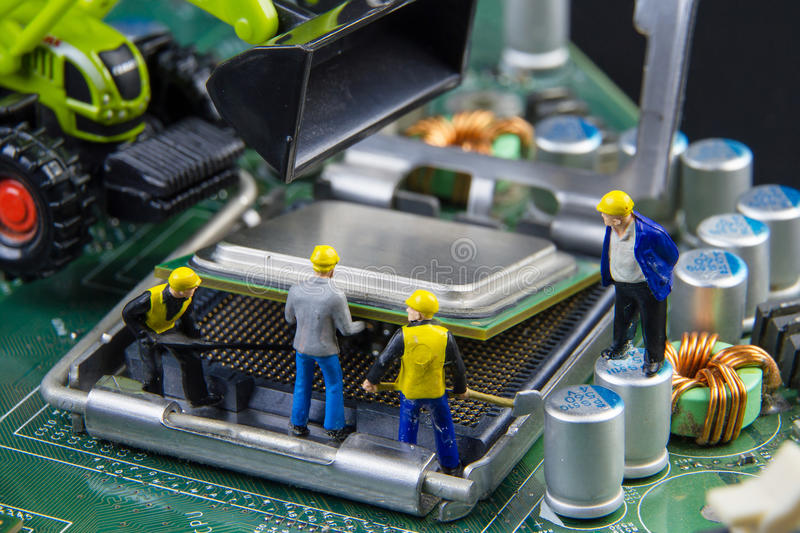 Miniature Engineers Fixing Error On Chip Of Circuit Board Focus On