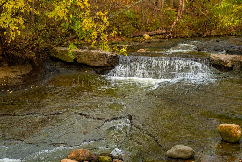 Tiny waterfall under autumn foliage stock photo