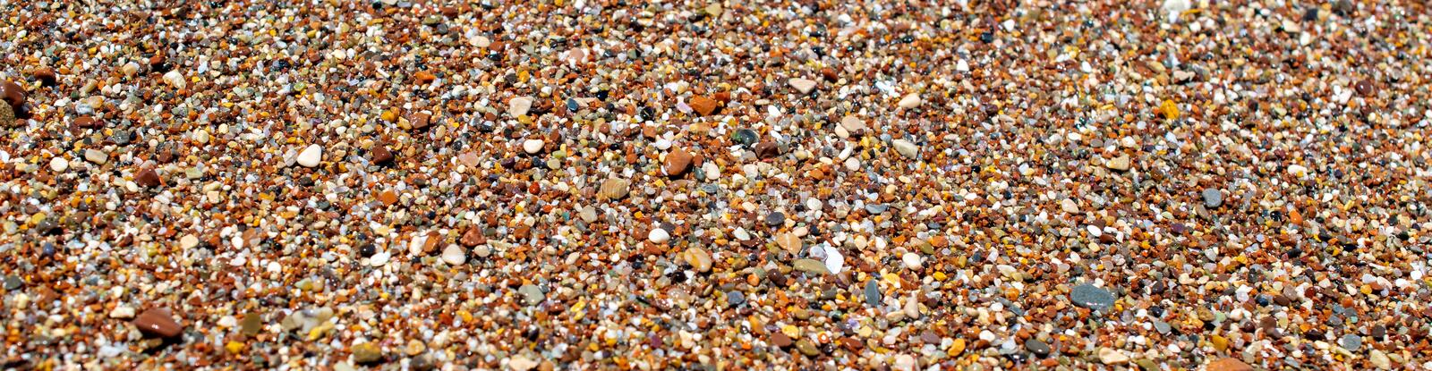 Tiny wet pebbles at the beach. Stone background image. Tiny colorful at the beach. royalty free stock images
