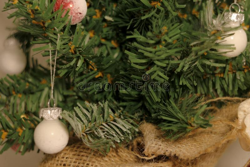 Tiny white Christmas baubles hanging in a miniature Christmas tree. Several tiny matte Christmas baubles hangs in a miniature indoor Christmas tree royalty free stock photos