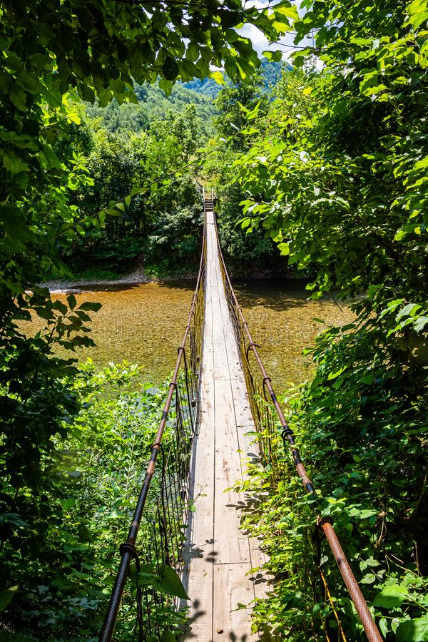 Tiny wooden and cable bridge above crystal clear water in river Neretva in village Ladanica, Bosnia and Herzegovina.  stock photos