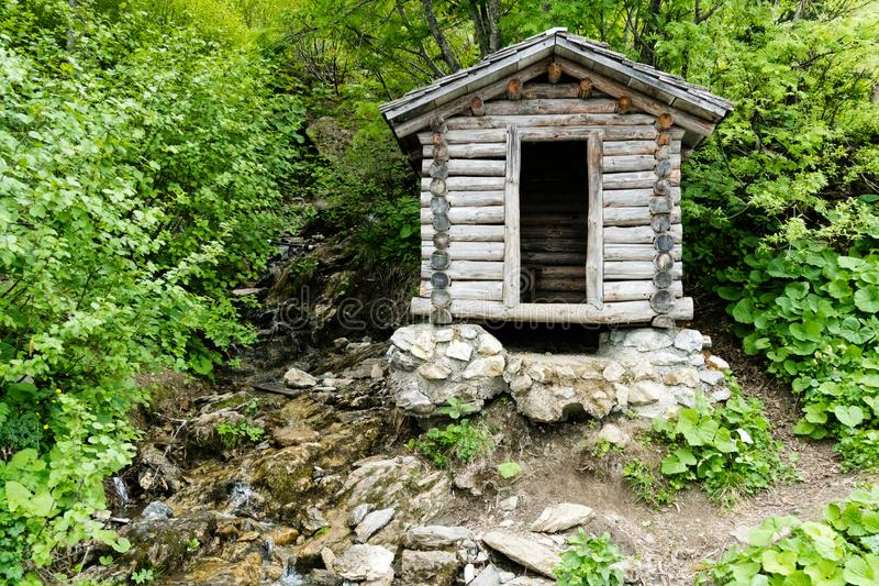 Tiny wooden mountain cabin in dense lush green summer forest with a small creek beside it royalty free stock images