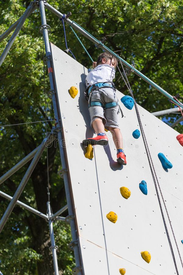 Tio år pojke som klättrar den utomhus- konstgjorda väggen med moderna färgrika håll arkivfoto
