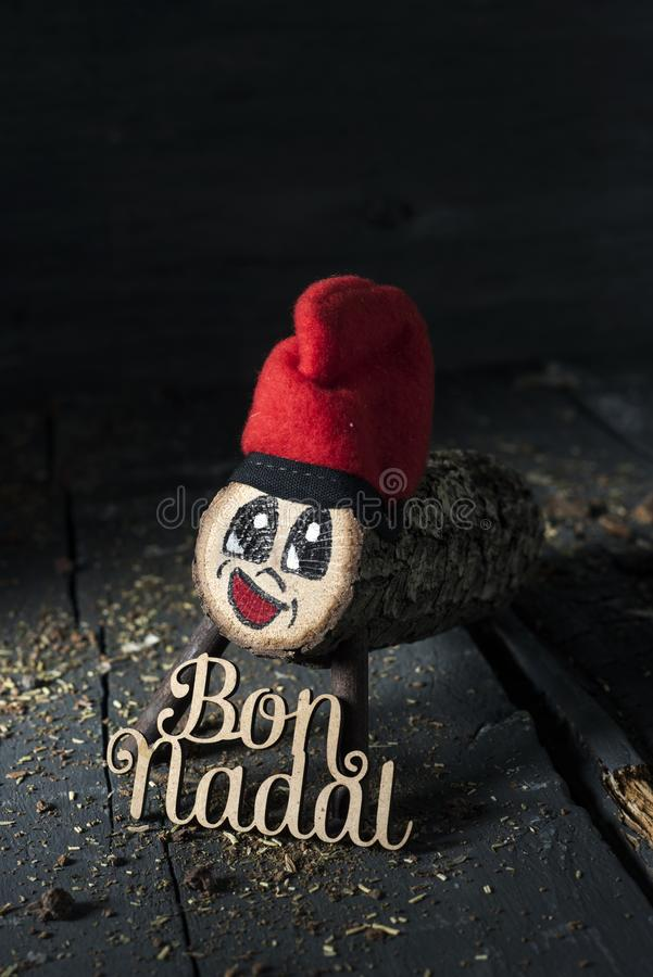 Tio de nadal and text merry christmas in catalan. A handmade tio de nadal, a typical christmas character of catalonia, spain, and the text bon nadal, merry stock photo