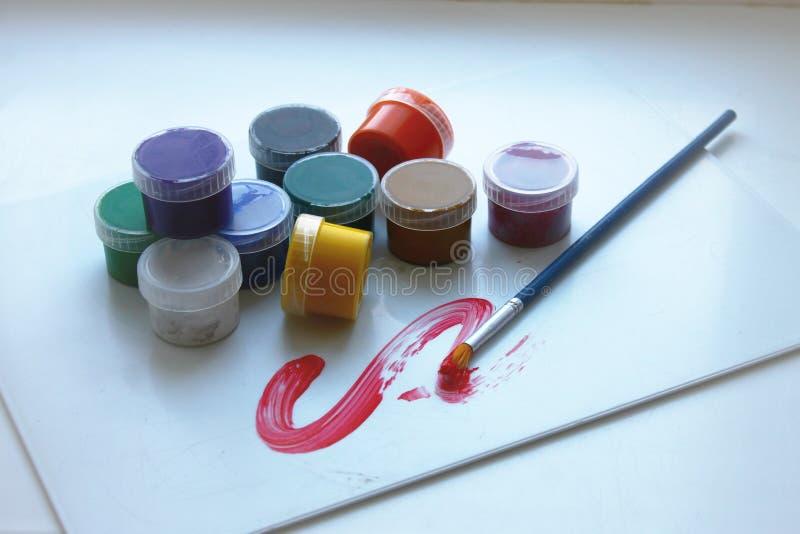 Tio färger i målarfärg på burk och en borste royaltyfri illustrationer