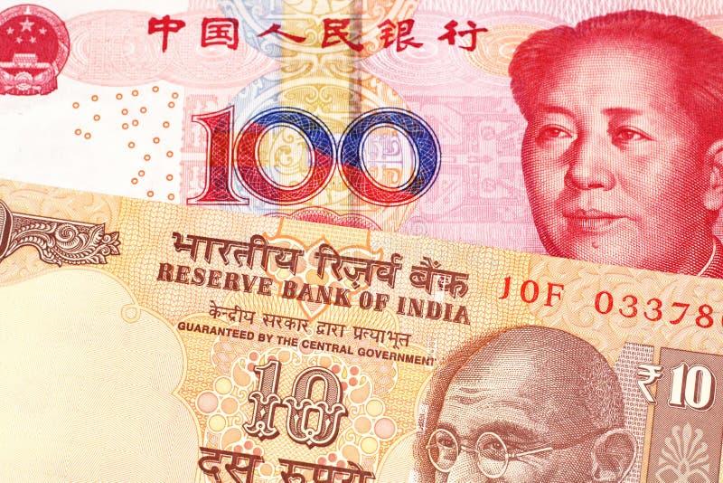 Tio indiska rupier med hundra kinesiska yuan arkivbild