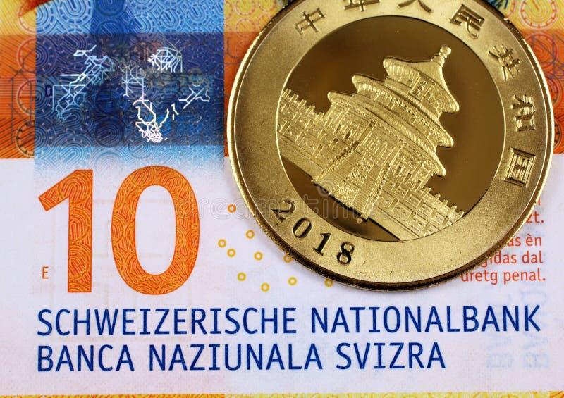 Tio schweizisk franc anmärkning med ett kinesiskt guld- pandamynt fotografering för bildbyråer