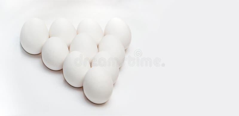 Tio vita ägg på en vit bakgrund i form av en triangel sund mat Sund livsstil Protein och äggula i skalet royaltyfria bilder