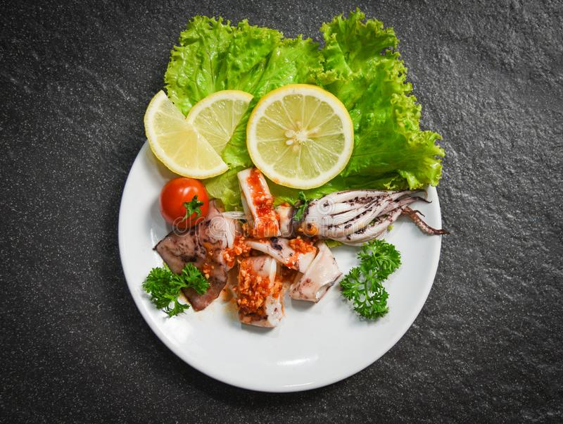 Tioarmad bläckfisksallad med kryddiga örter för chilisås och kryddor - grillad tioarmad bläckfiskskiva på plattan i den havs- res arkivbild