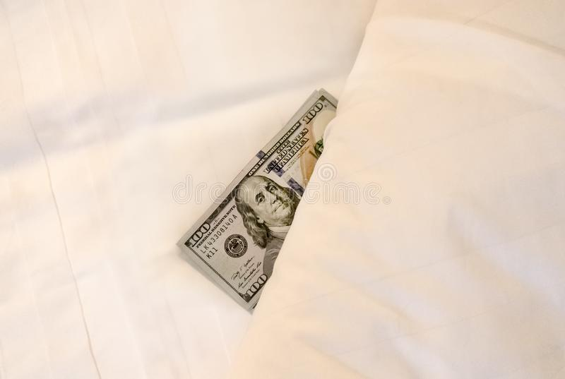 paying money dollar on white bed in hotel royalty free stock photography