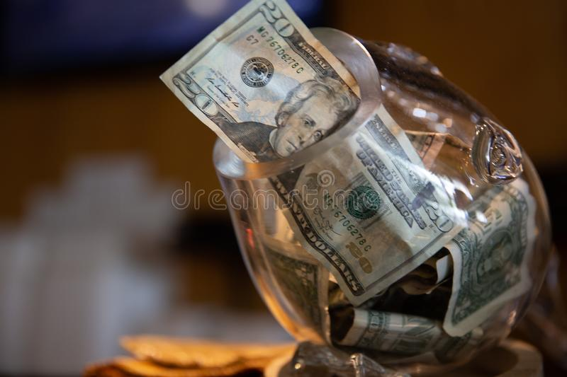 Tip jar with money in it - showing a twenty dollar bill. A glass tip jar at a sushi bar with money showing current tips and a twenty suggesting for more stock photography