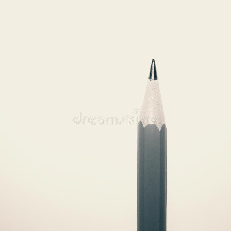 The tip of a sharp sharpened pencil. Against a light background. Macro, visible pencil, triangular shape, place for background stock image