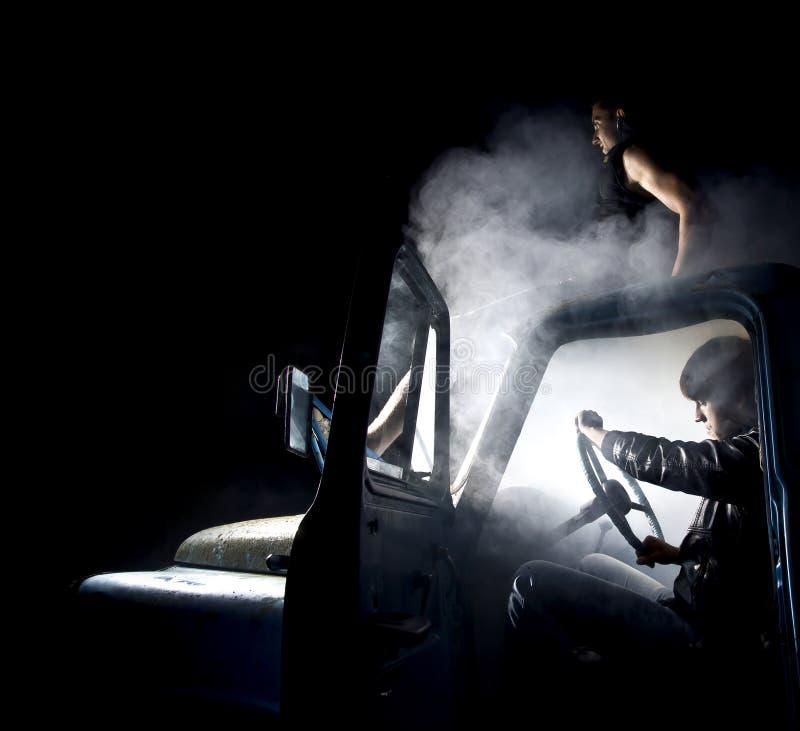 Tipi in automobile in pieno di fumo fotografie stock