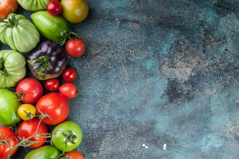 Tipi, colori e forme differenti di pomodori su un fondo concreto blu Raccolta del fondo dell'alimento Copi lo spazio fotografie stock libere da diritti