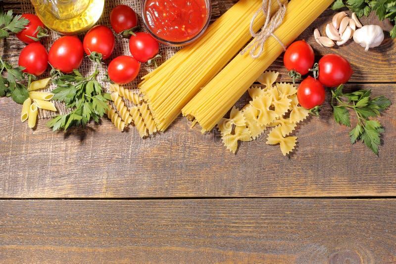 Tipi differenti di paste con i pomodori ciliegia, olio d'oliva, prezzemolo su un fondo di legno marrone fotografia stock libera da diritti