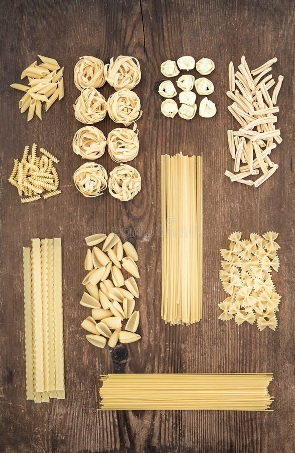Tipi differenti di paste crude italiane sul fondo di legno rustico della tavola, vista superiore immagine stock
