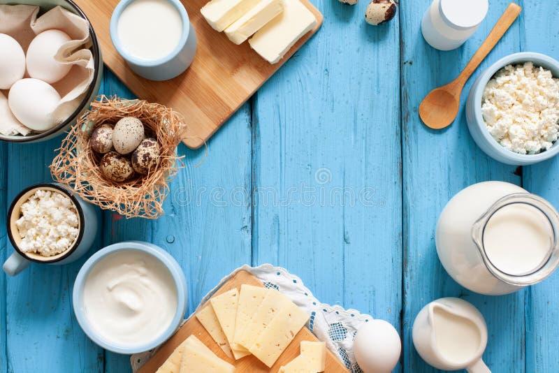 Tipi differenti di prodotti lattier-caseario su fondo di legno blu: latte, panna acida, ricotta, formaggio, crema, yogurt, uova e fotografie stock libere da diritti