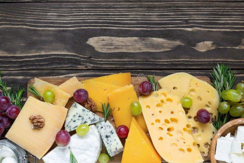 Tipi vari di formaggi sul tagliere di legno sulla tavola di legno rustica con l'uva ed i rosmarini fotografia stock