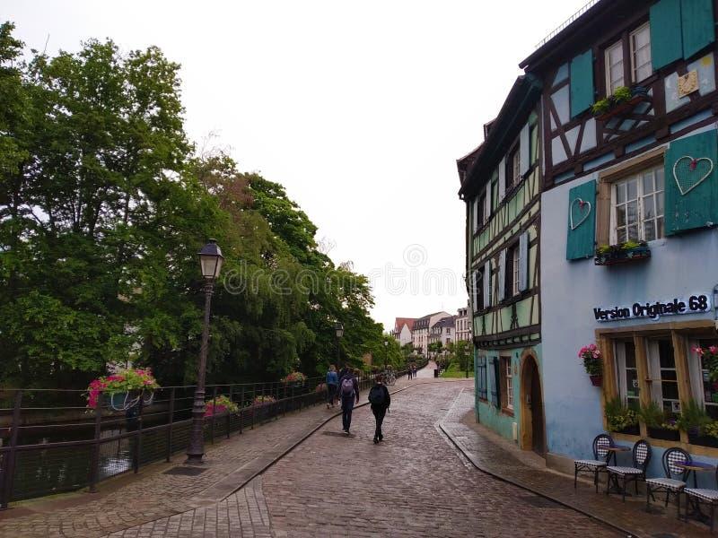 Tipical blauw huis in Rijnstijl naast Schilderachtig en verfraaid met bloemenkanalen van Colmar, Frankrijk stock afbeeldingen