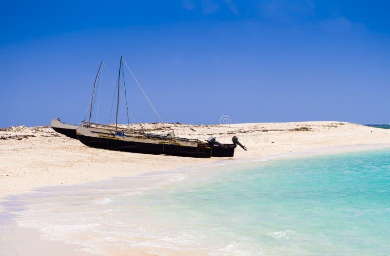 Tipici pinguelli di pescatori a spillo ormeggiati sul mare turchese dell'isola di Nosy Ve, nell'Oceano Indiano, in Madagascar fotografia stock libera da diritti