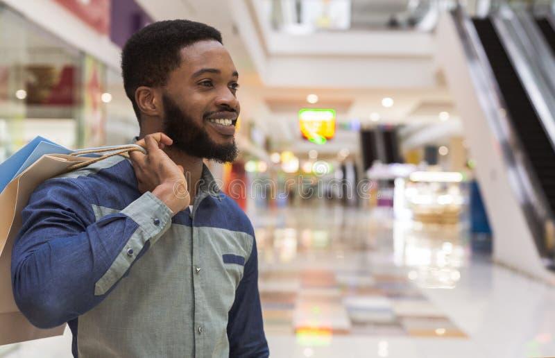 Tipo africano bello con i sacchi di carta felici dopo la compera fotografia stock libera da diritti