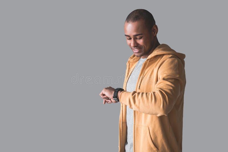 Tipo africano che fissa al suo orologio della mano fotografia stock