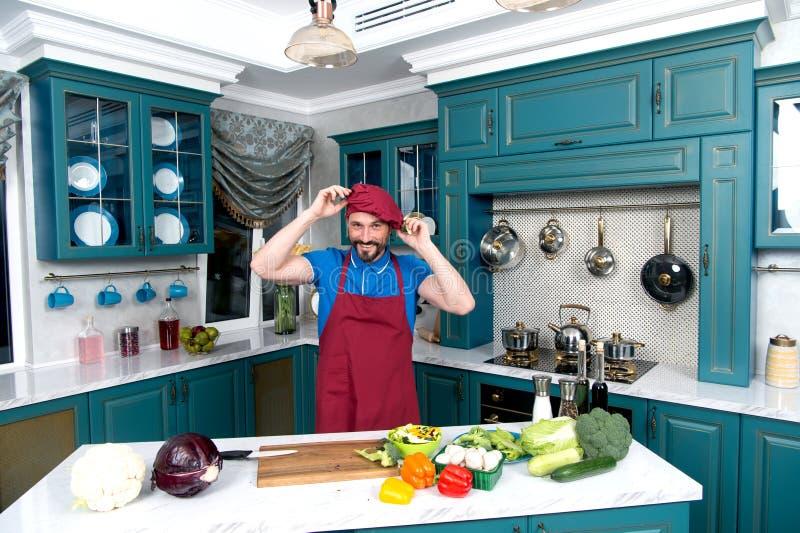 Tipo alla cucina che veste grembiule e cappello Il cuoco unico porta l'uniforme di rosso Uomo vestito sul cappello rosso a dispos fotografia stock