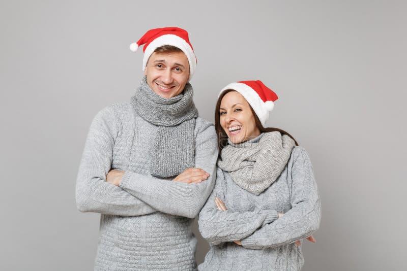 Tipo allegro della ragazza delle coppie di divertimento in sciarpe grige dei maglioni del cappello rosso di Santa Christmas isola fotografie stock