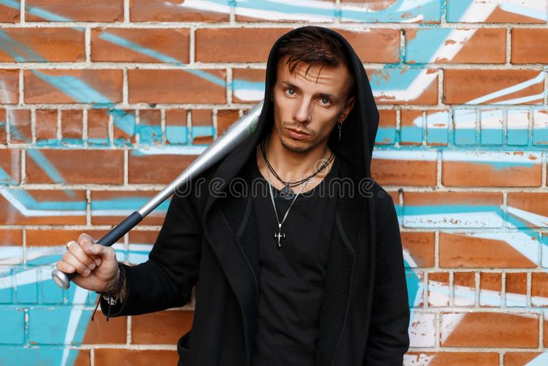 Tipo arrabbiato vicino al muro di mattoni con i graffiti che tengono un pipistrello del metallo fotografie stock