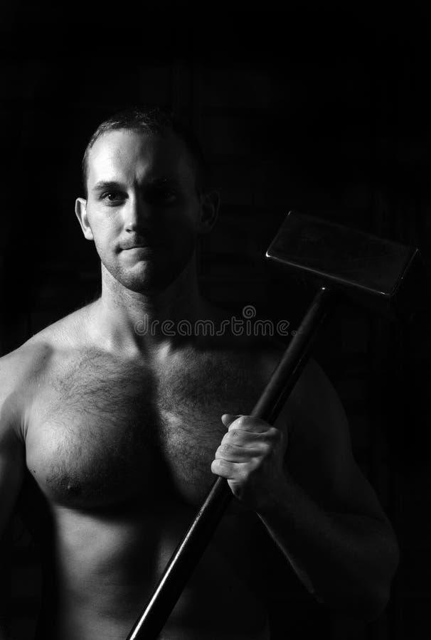 Tipo atletico che tiene un martello sulle sue spalle fotografie stock libere da diritti
