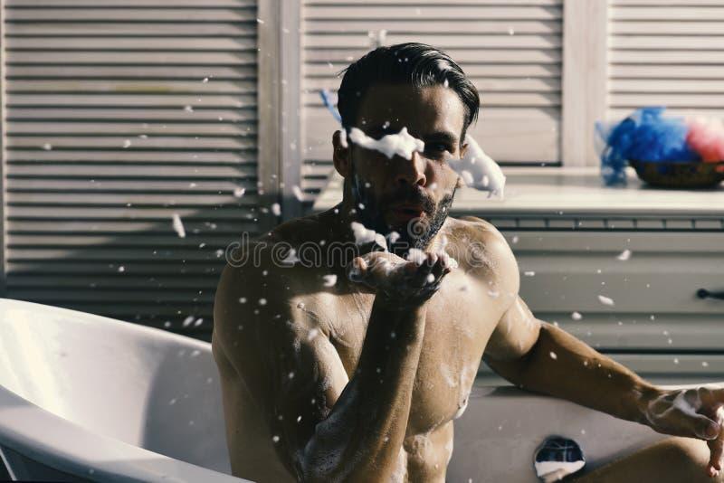 Tipo in bagno coperto di schiuma con gli articoli da toeletta e le scale su fondo Seduta macho nuda in vasca come erotica fotografia stock