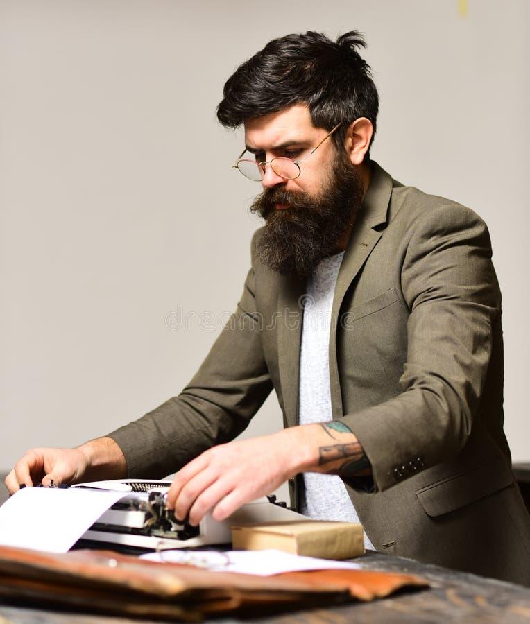 Tipo barbudo del hombre en la máquina de escribir El hombre con la barba larga y el bigote escriben el trabajo de investigación a fotografía de archivo