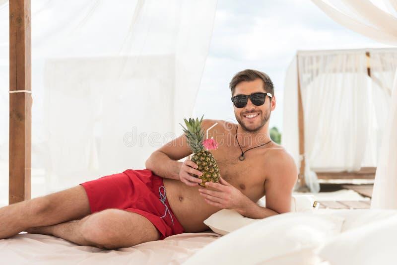 Tipo barbuto giovanile di buon umore che si rilassa sulla spiaggia di estate fotografia stock libera da diritti