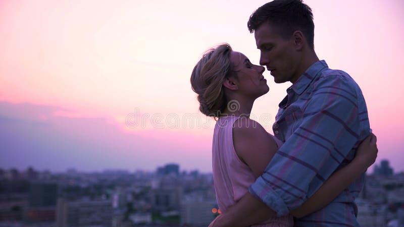 Tipo bello che abbraccia tenero la sua bella signora sul terrazzo aperto, paesaggio urbano immagine stock libera da diritti