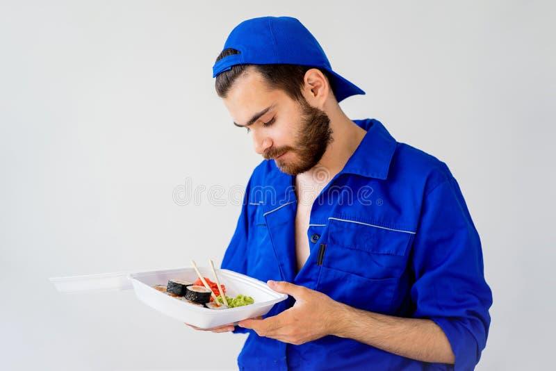 Tipo bello che consegna i sushi fotografia stock